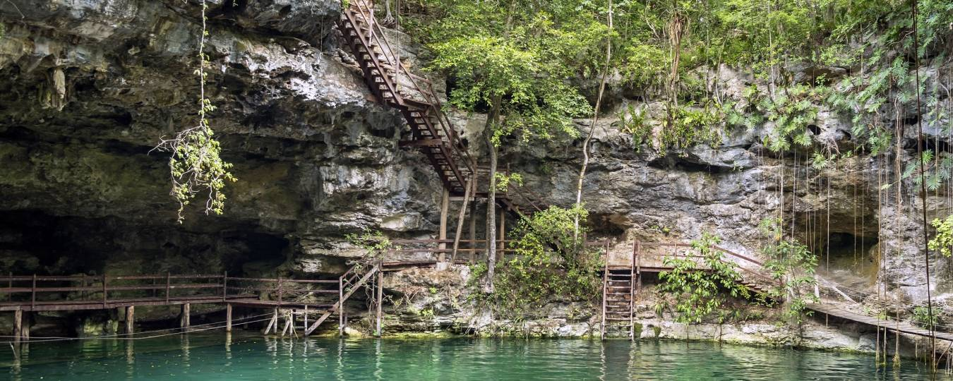 Mayan cenote with cliff steps to water