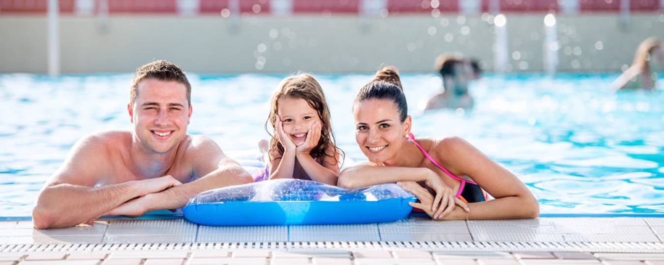 Family playing in pool having good time