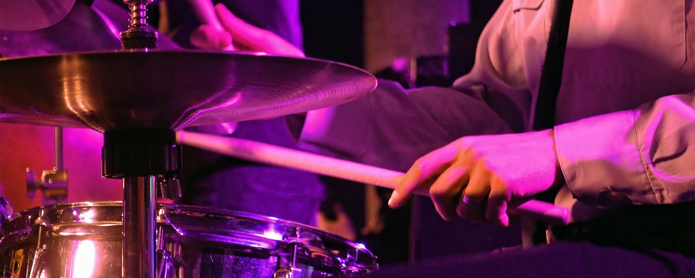 Drummer Playing On Purple-Lit Drums