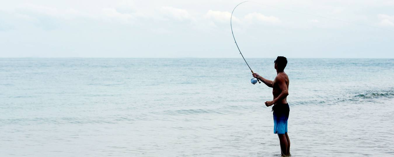 Man fly fishing on beach in Tulum