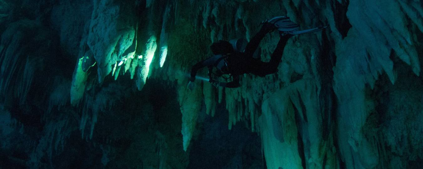 Under Water Scuba Diver with Stalagmites and Stalagtites