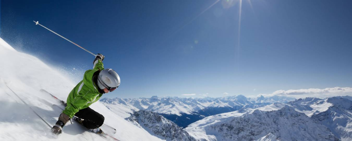 Skier on a Steep Slope with Blue Skies