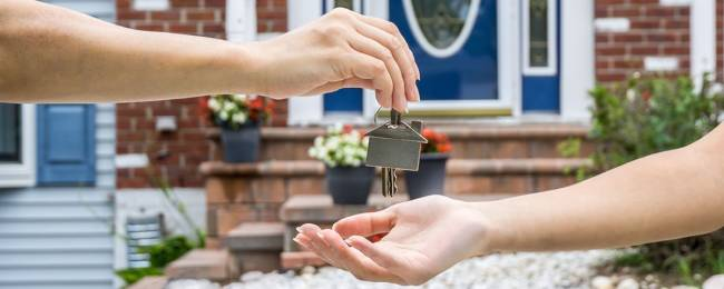 Property manager giving key to vacation renter