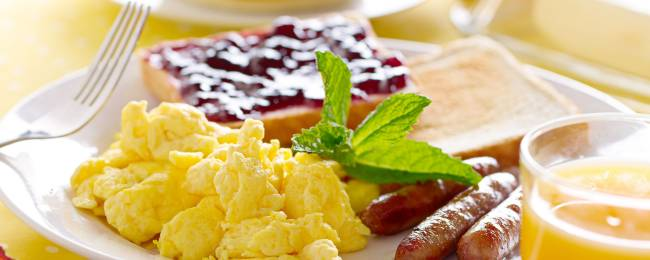 Breakfast plate with toast, jelly, and eggs served with orange juice.