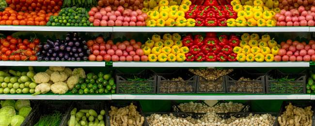 Produce including bell peppers, cucumbers, and lettuce on a grocery store shelf.
