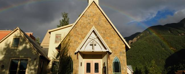 Outside of Alpine Church with a rainbow in the sky.