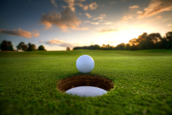 Golf Ball Near the Hole with a Stunning Sunset in the Background