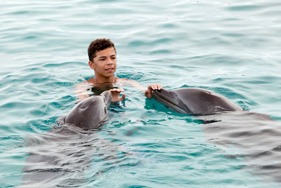 Boy Swimming with Dolphins