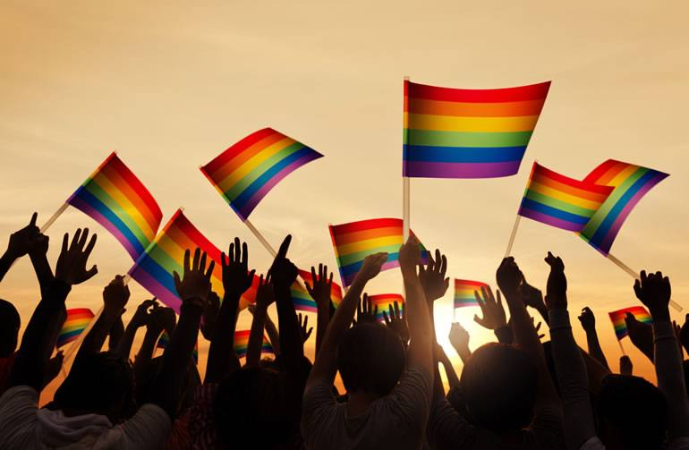 LGBT Flags and Hands at Sunset