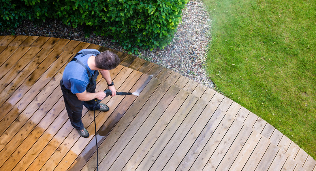 Man deep-cleaning outdoor deck