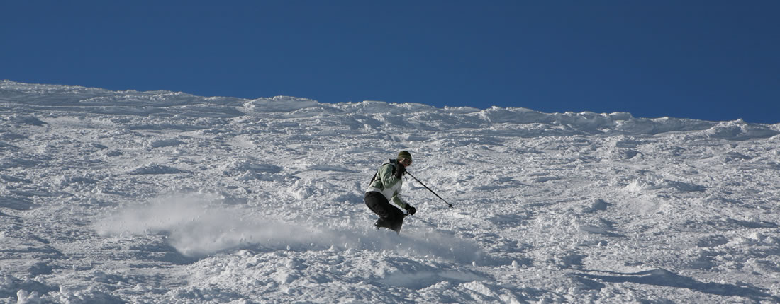 Skier going down crud snow in Telluride
